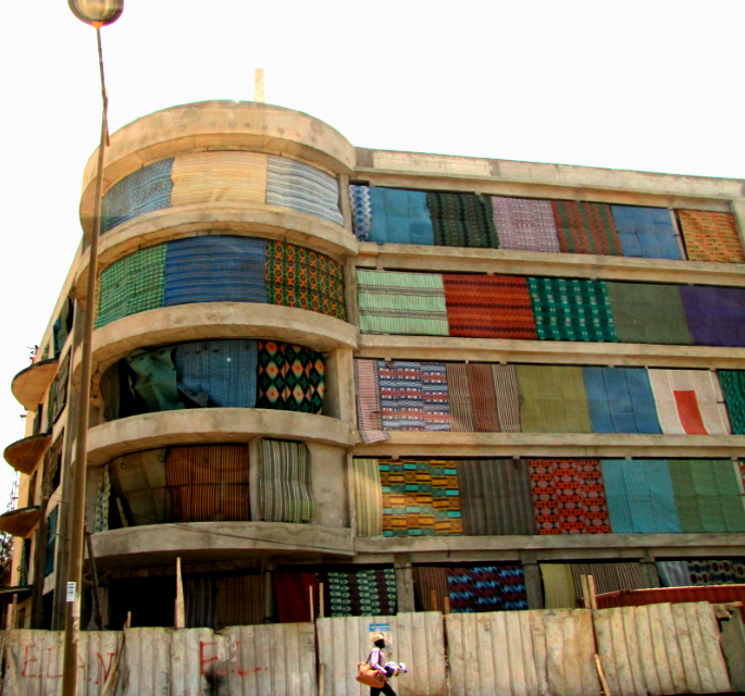 Woven mats hanging from a building under construction
