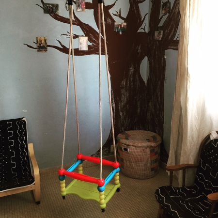 Toy basket, bogolafini mud cloth meets IKEA and yard sale chairs, and possibly the most brilliant kids' room hack ever: securely mounted D-rings in the ceiling. We have this child's swing, a trapeze bar and a hanging bubble chair. Just swap them out every few months and they love it.